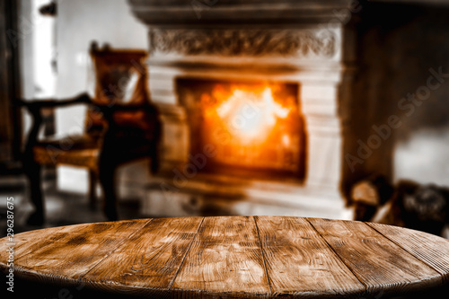 Slika na platnu Table top with blurred fireplace and cosy home interior background