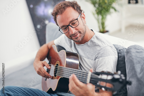 Man playing acoustic guitar in the living room. - 296288257