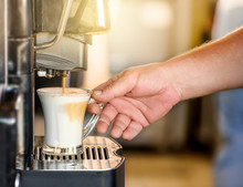 Hand Taking Coffee Cup In Automated Coffee Making Machine.