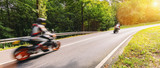 Fototapeta Na ścianę - motorcycles on the forest road riding fast. having fun driving the empty road on a motorcycle tour journey. copyspace for your individual text.