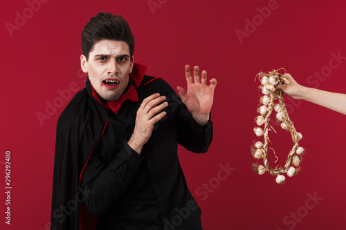 Image of young vampire man in halloween costume being scared of garlic Wallpaper Mural