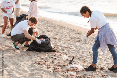 Image of kind volunteers cleaning beach from plastic with trash bags Wallpaper Mural
