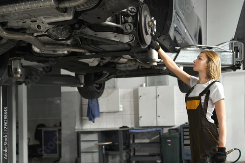 Woman in coveralls fixing brake discs of lifted car. - 296298648