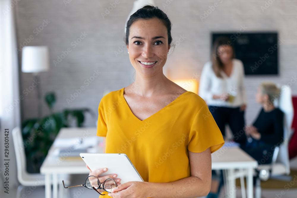 Fototapeta Pretty young businesswoman looking at camera. In the background, her colleagues working in the office.