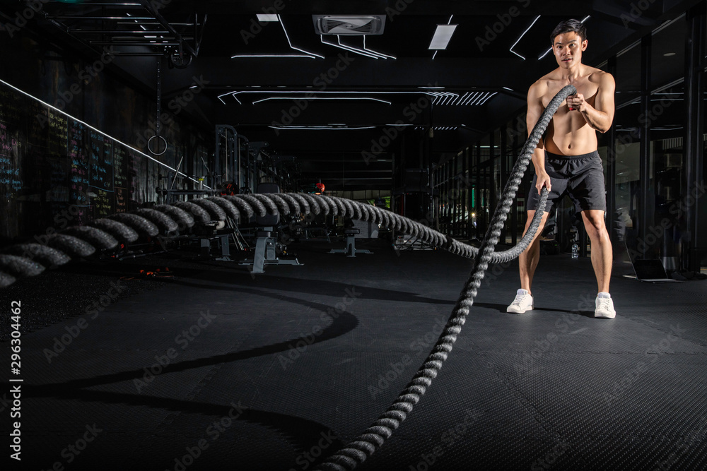 Fototapety, obrazy: Handsome muscular man is doing battle rope exercise while working out in gym