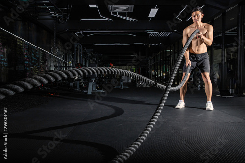 Fotografie, Obraz  Handsome muscular man is doing battle rope exercise while working out in gym