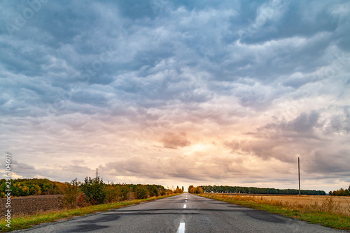Road under cloudy overcast skies at sunset Canvas Print