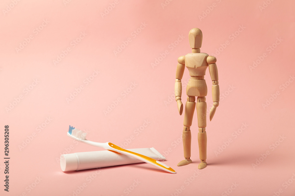 Fototapety, obrazy: Oral hygiene and dental care. Wooden man holds toothbrush and toothpaste.