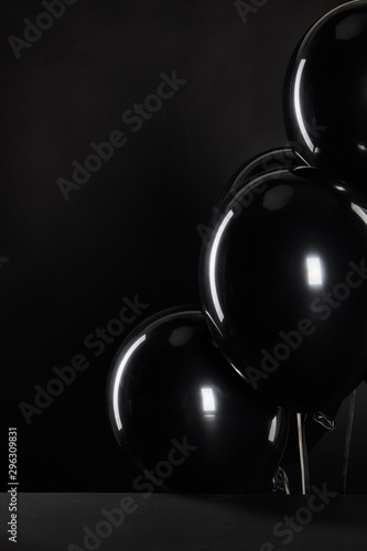 Photo bunch of black balloons isolated on black, black Friday concept