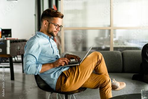 Fotomural  Young smiling Man typing on laptop