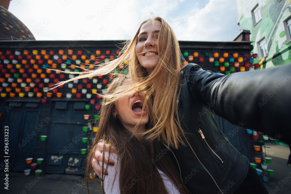 Fototapety, obrazy: two very cute young girls posing as top models on a street in Europe on vacation,sisters actively posing on a sunny summer day ,very happy and joyful people