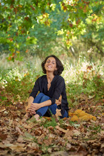 Latin Brunette Woman With A Black T-shirt In A Forest With Dry Leaves And Autumnal Colors, The Sun Enters Between The Branches Of The Trees, She Is Sitting With A Notebook In Her Hands.