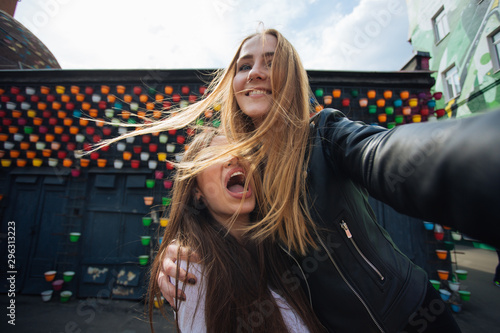 Fotomural  two very cute young girls posing as top models on a street in Europe on vacation