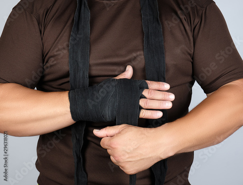 man wraps his hands in black textile bandage for sports Canvas-taulu