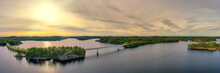 Aerial Panorama View Of Modern Bridge With Cars Across Blue Lake Saimaa At Summer Sunset Time. Beautiful Sky With Clouds. Finland