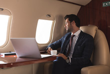 Pensive Businessman Holding Cup Of Coffee In Plane With Laptop During Business Trip