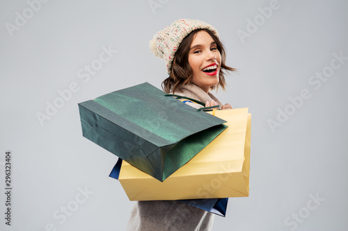 Fototapeta christmas, seasonal sale and consumerism concept - happy smiling young woman in knitted winter hat and sweater with shopping bags over grey background obraz