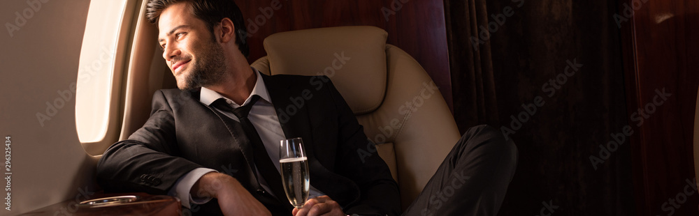 Fototapeta handsome cheerful man holding glass of champagne in plane