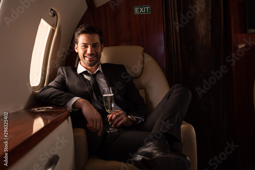 handsome smiling man holding glass of champagne in plane