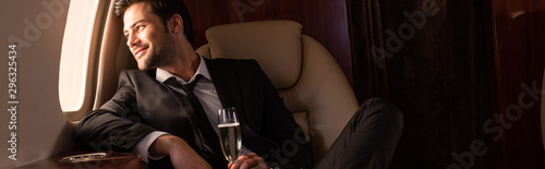 Cuadros en Lienzo  handsome cheerful man holding glass of champagne in plane