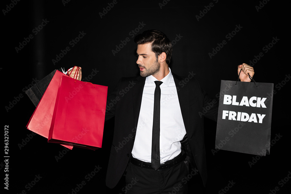 Fototapeta elegant man holding shopping bags with black friday sign, isolated on black