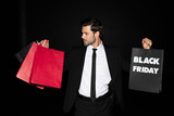elegant man holding shopping bags with black friday sign, isolated on black