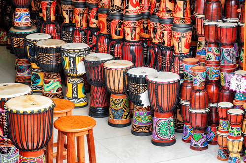 Poster de jardin Magasin de musique Wide range of colorful djembe drums at souvenir shop