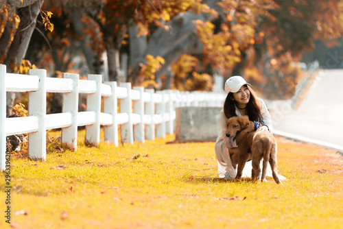 Foto  Asian lifestyle woman playing and hug young golden retriever friendship dog in outdoor the autumn nature park