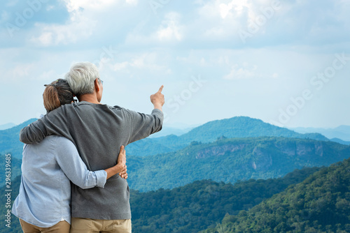 Poster Detente Asian Lifestyle senior couple hug and pointing the mountain nature. Old people happy in love romantic and relax time. Tourism family elderly retirement travel in summer leisure and destination.