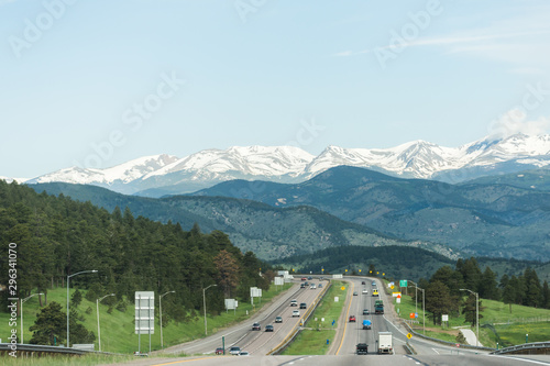 American highway going through snow capped mountain landscape Wallpaper Mural