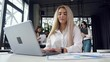 Close up of charming industrious blond businesswoman working at the workplace with documents and computer