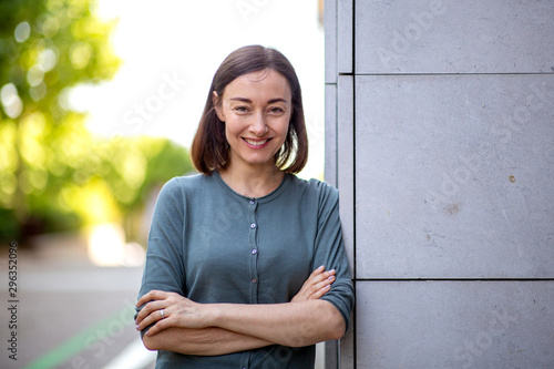 Cuadros en Lienzo beautiful middle aged woman leaning against wall and smiling with arms crossed