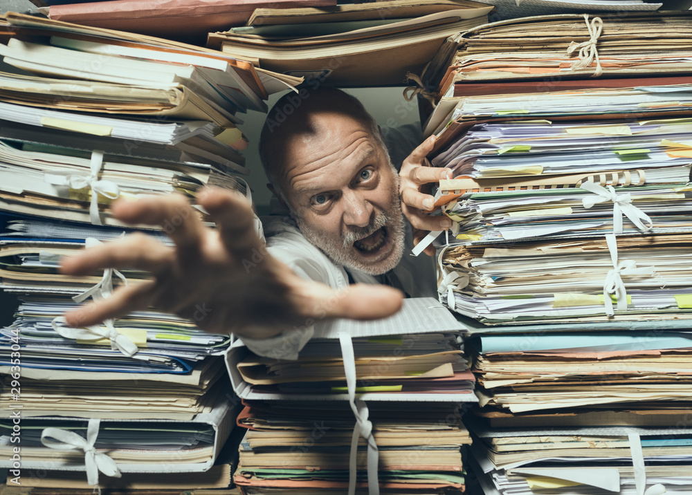 Fototapeta Panicked businessman overloaded with paperwork