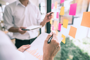 Business people meeting at office and use sticky notes on glass wall in office, diverse employees people group planning work together brainstorm strategy.