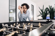 Businessman With Ball At Foosball Table In Office