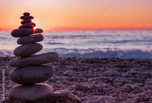 Poster de jardin Zen pierres a sable The object of the stones on the beach at sunset. Sunlight between the stones. Zen concept. Sunset.