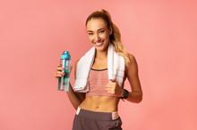 Smiling Girl Standing Holding Bottle Of Water, Studio Shot
