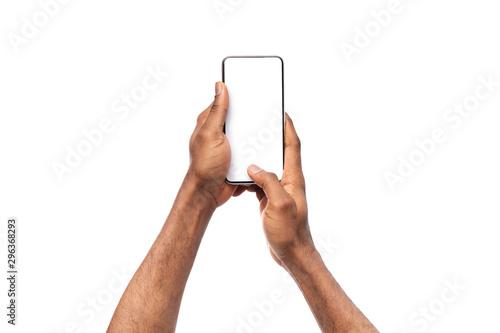 Fototapeta Black man's hands holding cellphone with blank screen, taking photo obraz