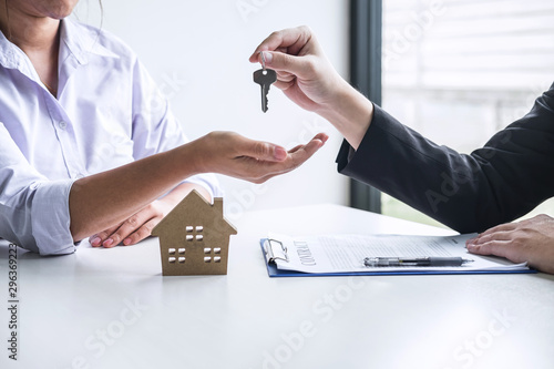 Estate agent giving house keys to client after signing agreement contract real estate with approved mortgage application form, concerning mortgage loan offer for and house insurance