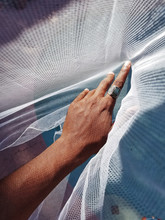 Selective Focus Of Hand With Ring Holding White Mosquito Net