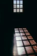 Sunlight Through Window Panes In Dark Room