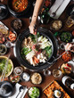 Overhead view of hands reaching for Asian food on table