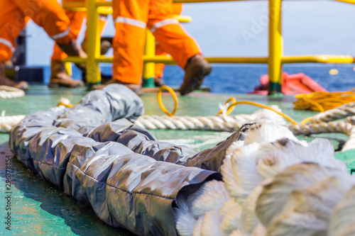 Fotografia Offshore worker preparinf hawser rope for anchor mooring to platform jacke leg