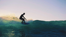 Silhouette Man Surfing On Wave At Dawn