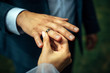 Young bride put a gold wedding ring on the groom's finger, close-up. Wedding ceremony, exchange of rings.