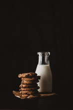 Choco Chip Cookies On Unbleached Parchment Paper With Bottle Of Milk