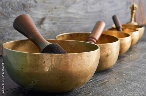 Obraz na plátně Tibetan singing bowls with sticks on the dark background - music instruments for