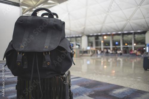 Backpack put on top of a black hand luggage case at the airport, waiting for flight Billede på lærred