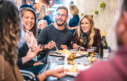 fototapeta na lodówkę Young friends having fun drinking white wine at street food festival - Happy people eating local plates at open air restaurant together - Travel and dinning lifestyle concept on bulb light neon filter