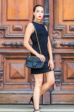 South American Businesswoman Working In New York City. Young Hispanic Woman Wearing Black Sleeveless Dress, Shoulder Carrying Black Leather Bag, Walking Dow Stairs By Brown Vintage Wooden Office Door.